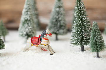 Christmas card - a miniature Christmas tree and rocking horse / nutcracker in the snow - winter