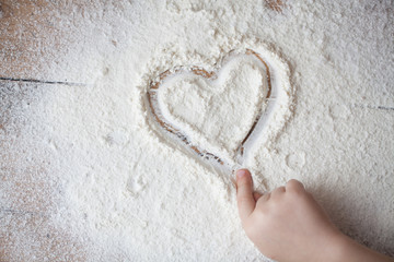 Heart of flour on wooden desk painted by a child