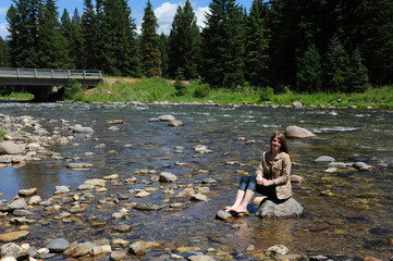 Young woman poses barefoot in Gallatin River.  She sitting on a rock and smiling.  Bridge is in background.