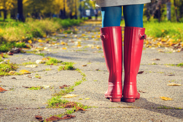 Young woman in pink rain boots walking. Close up of boots.