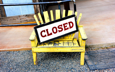 Closed sign sits in front of business.  It is resting on rustic, yellow bench.  Welcome sign sits besides it.