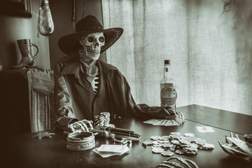 Old West Poker Skeleton. Old west bandit outlaw skeleton at a poker table with a pistol and bourbon, edited in vintage film style.