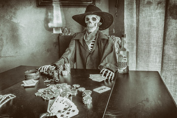 Old West Poker Playing Skeleton. Old west bandit outlaw skeleton at a poker table with a pistol and bourbon, edited in vintage film style.