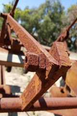 Corroded metal joints with rusty bolt and nuts of old agriculture equipment at farm backyard