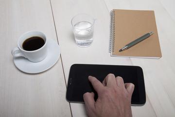 Hand zeigt auf einen Tablett PC der auf dem Arbeitstisch liegt i