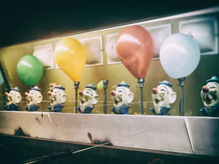 Water Gun Clown Carnival Game Balloons Retro. Classic water gun clown balloon carnival game. Old, aged looking clown heads and lights. Squirting and balloons. Edited with a vintage film effect.