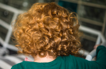 Back of head little girl with glossy red curled hair. Closeup of ginger haired kid with glossy curls, perfect for family blog, website, magazine