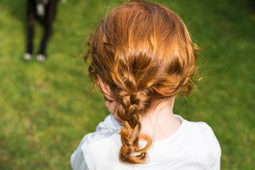 Back of head little girl with long red curled hair. Closeup of ginger haired female child with glossy curls, perfect for family blog, website, magazine