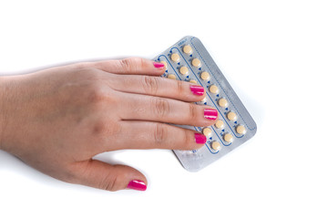 young woman hand with pink nail polish  holding a contraceptive pills blister, white background