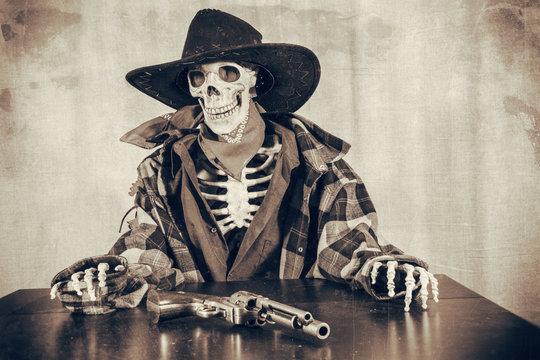 Old West Skeleton Revolver. Old west bandit outlaw skeleton at a poker table with a colt 45 pistol revolver edited in vintage film style.