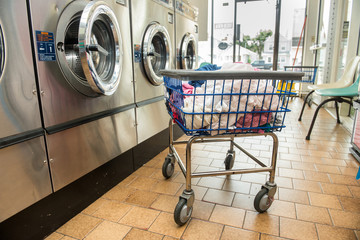 Industrial washing machines in a public laundromat, with laundry in a basket