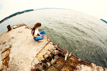 Young woman using smartphone sitting on an old  pier. Image retro vintage filter effect