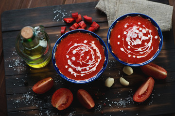 Bowls with tomato soup gazpacho on a rustic wooden surface