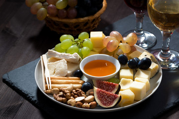 Plate with deli snacks and wine on a dark background, closeup