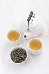 teapot and cups of green tea on a white wooden background