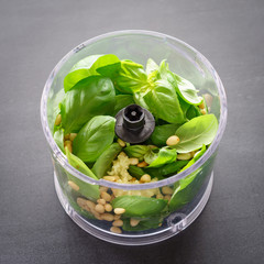Ingredients for pesto sauce in food processor. Selective focus