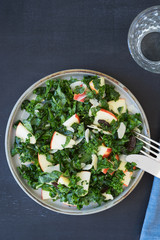 Kale salad with apples, almond slices and raisins. Overhead view
