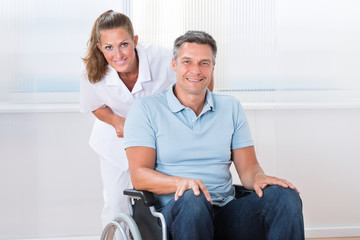 Doctor Carrying Patient On Wheelchair