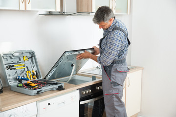 Repairman Examining Stove In Kitchen Wall mural