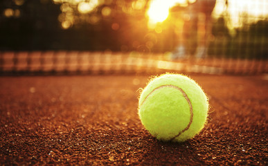 Tennis ball/Close up of tennis ball on clay court.