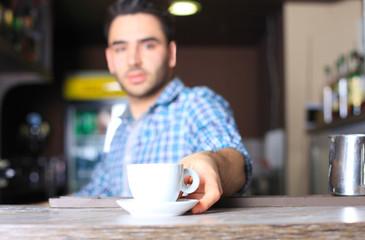 Barista prepares cappuccino in his coffee shop. Close-up cup of coffee