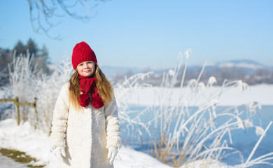 Little adorable girl in winter hat in snow forest