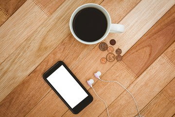Coffee and black smartphone with white headphones