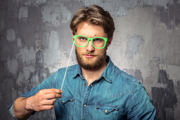 Young handsome man holding paper green glasses