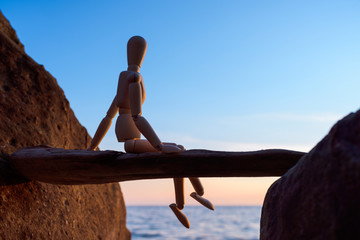 Wooden mannequin between boulders