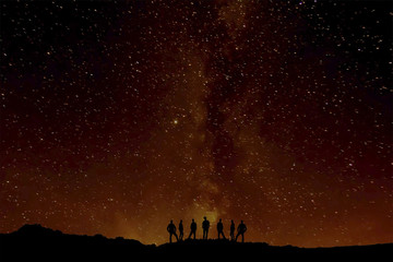 Group of people silhouette, with sky at night with stars on background, brilliant background; similar to the eruption of a volcano, abstract photography
