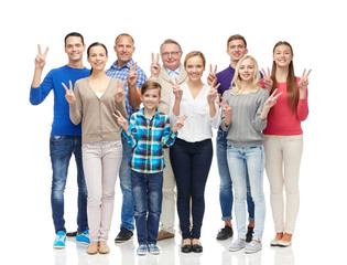 group of smiling people showing peace hand sign