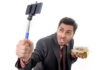 businessman taking selfie photo with mobile phone camera and stick posing happy and successful with gold bar and money