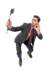 young attractive businessman in suit and tie taking selfie photo with mobile phone camera and stick posing happy