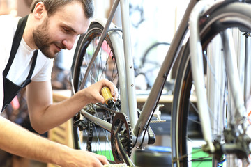 Mechaniker repariert Fahrrad in einer Werkstatt - ölen der Kette // mechanic repaired bicycle in a workshop