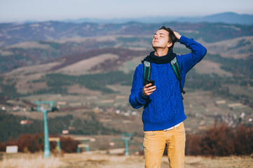 Young hipster taking photo by smart-phone on the peak of mountai
