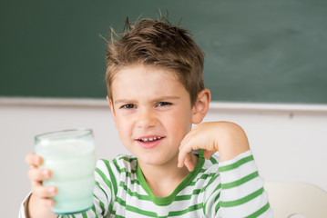 Kleiner Schuljunge trinkt ungern Milch