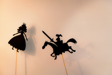 Shadow puppets of Princess and Knight and their shadows on the bright glowing screen of shadow theatre. Copy space background.