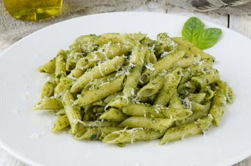 Pasta with pesto sauce on white plate