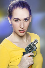 female power concept - intimidating young woman with tied hair showing a handgun for impressing or expressing self-protection,retro light effects