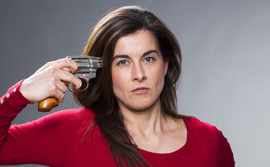 female power concept - carefree 30s woman pointing a gun to her head for serious suicide concept or expressing distress