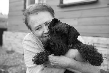 Portrait of an old woman holding black dog