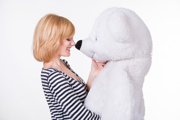 Beautiful young woman playing with big white teddy bear. White background