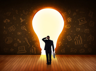 Business man looking at bright light bulb in the wall