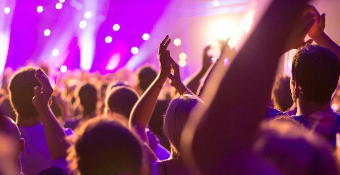Nachts: Ein Konzert, eine Party,  Menschen sind fröhlich, feiern und haben Spaß an der tollen Musik, sie klatschen Beifall