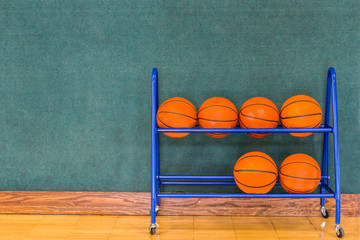 Basketballs in Storage Rack against Wall in Gym Basketball Court.  Copy Space.