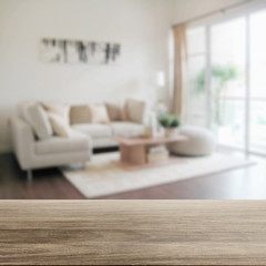 wooden table top with blur of modern living room interior