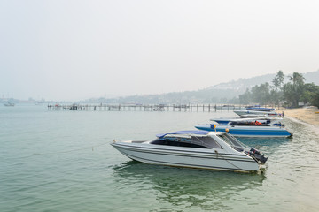 Speed Boats moored on tropical sea in Samui Island,Thailand with foggy sky.