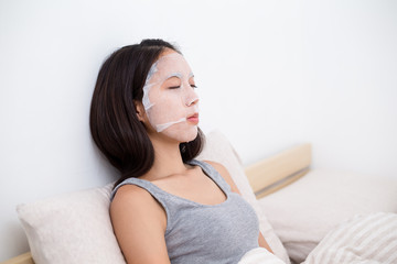 Woman sitting on bed and using the paper mask