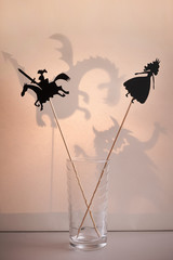 Shadow puppets in the glass with a soft glowing screen of shadow theatre and monsters shadows in the background.