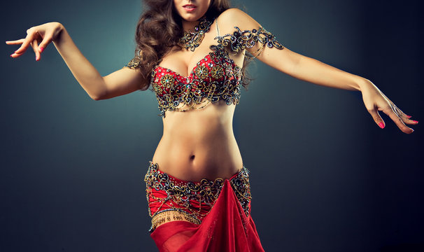 Graceful girl dancing belly dance . Belly dance in plastic movement of the dance. Red dress for belly dance with sequins and rhinestones and jewelry